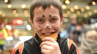 Boy with body art drawing on the face eating gingerbread cookies
