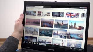 Browsing photo of London in Google - man using Laptop planning travel