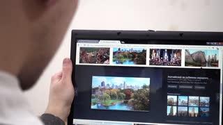 Browsing photo of New York in Google - man using Laptop planning travel