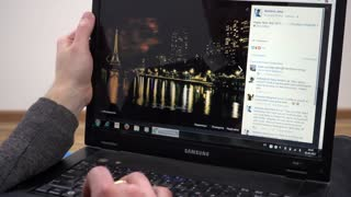 Browsing photo of Paris in Facebook - man using Laptop planning travel
