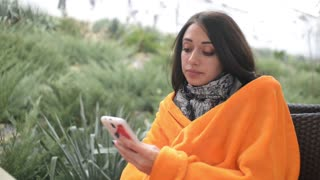 brunette woman with mobile phone at an outdoor cafe wrapped blanket