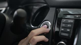 Business Woman in a new car Nissan push the Button of Starter