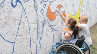 Children disable on a wheelchair draws paint on the fence wall