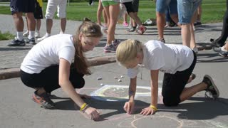 Children draw with chalk on the pavement