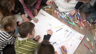 Children draw with markers on a large paper