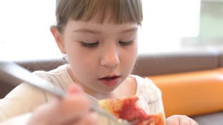 Children eating pizza by hands