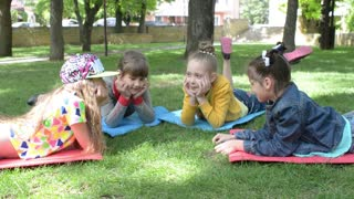 Children lie on the green grass - a picnic in the park