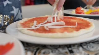 Children make a pizza with his own hands in the restaurant