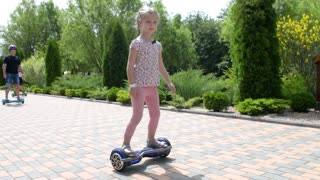 Children ride on a Segway motorized scooters hoverboard in the park
