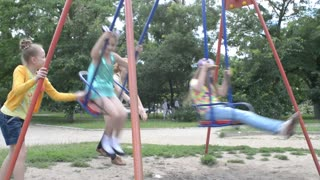 children swinging on the swings at the playground in the park