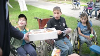 Children with physical development disorders on wheelchairs eating cookies
