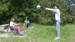 Children with physical development disorders on wheelchairs play ball in a yard