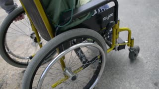 Children with physical development disorders on wheelchairs play in a yard