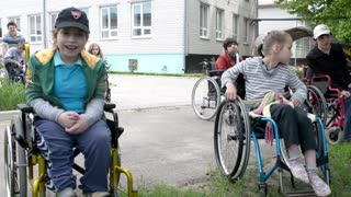 Children with physical development disorders on wheelchairs smiling to a camera
