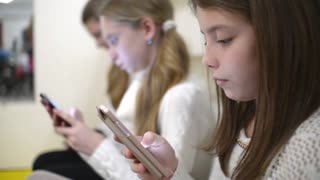 Children with their Smartphones and mobile phone in school class room shatting