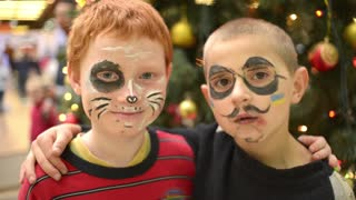 Christmas Decorations - Boys with Body art drawing on the faces - happy children