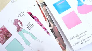 Close-up - Fashion Designer shows his Sketches a new Collection of Clothes