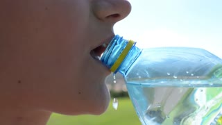 Close up Of Woman Drinking Water From Plastic Bottle