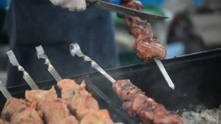 Cooking eating meat barbecue on the street food festival