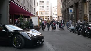 Croud of people in center of Milan walking, expensive car  - spring day