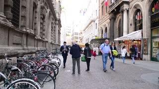 Croud of people in center of Milan walking looking in showcase shop - spring day