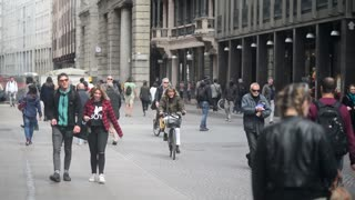 Croud of people in center of Milan walking looking in showcase shop - spring day