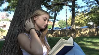 Cute Blonde Girl reading a Book during a Picnic in the Park sunny Day