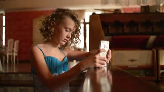 Cute girl in elegant dress with mobile phone takes Selfie Photo at restaurant