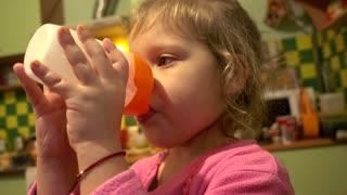 cute little child girl drinking from plastic bottle