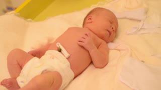 dressing newborn baby in the maternity hospital