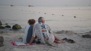 elderly couple man and woman on the beach sitting on the sand