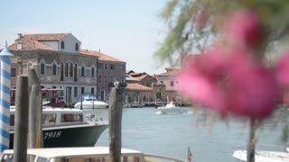 Embankment and pier in Venice, on the island of Murano - boats and flowers
