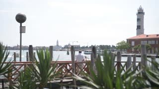 Embankment and pier in Venice, on the island of Murano - people and flowers