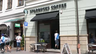 Facade of cafe Starbucks coffee - people come inside Krakow old town day
