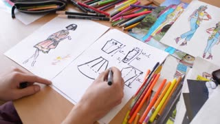 Fashion designer is working on a new collection, making sketches