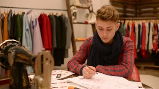 Fashion designer is working on a new collection , making sketches