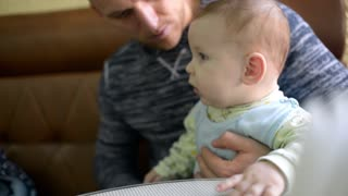Father and baby boy rest at the cafe