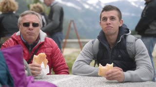 Father and son eating sandwiches on the background of the Alps.