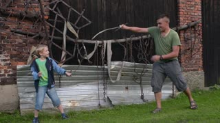 Father and son fighting saber in the backyard