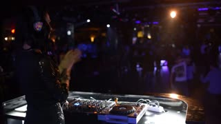 Female Dj Is Performing Her Set, people dancing In The Night Club