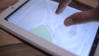 Female Hand looking at the Digital Tablet Google Maps street address