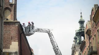 fire brigade on lift ladder repairing the roof old building - Krakow Poland