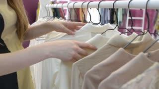 Girl brunette get shopping at store, coats, dresses, blouse on the trempels