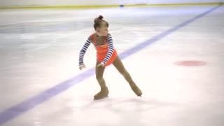 Girl Child Figure skating on ice rink.