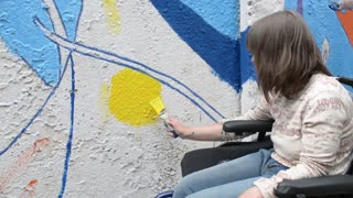 Girl disable on a wheelchair draws paint on the fence wall