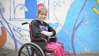 Girl disable on a wheelchair smiling with brush in hand
