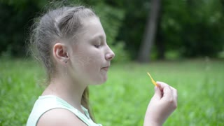 Girl eats potato chips on a picnic in the park