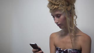Girl Fashion Model chating sms with Mobile Phone communicate in Beauty salon
