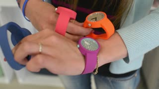 Girl get shopping in a store chooses Wrist Watch O Bage