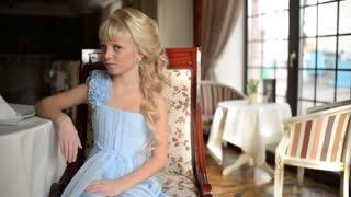 Girl in an elegant dress waiting at the restaurant against window
